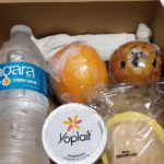 prepackaged breakfast box with water bottle, orange, yogurt and muffin